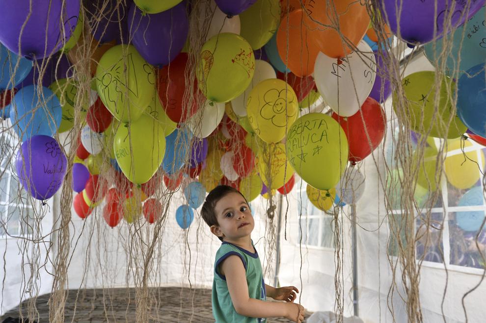 """Un copil se joacă printre baloane colorate, cu mesaje scrise de părinţi ai căror copii au decedat, în timpul celei de-a şaptea ediţii a evenimentului """"Ziua Părinţilor de Îngeri"""", organizat de Organizaţia E.M.M.A, în Bucureşti, duminică, 8 iunie 2014."""