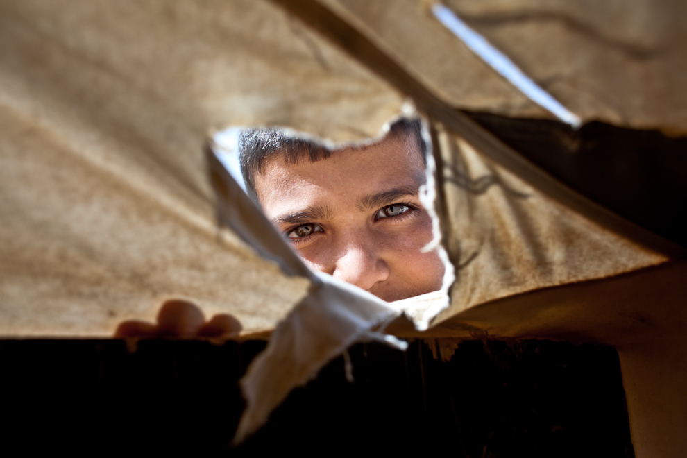 Un băiat sirian priveşte prin gaura unuia dintre corturile în care refugiaţii trăiesc în Za'atari, cea mai mare tabără de refugiaţi sirieni din Iordania şi a doua din lume. În urma afluxului de refugiaţi, Za'atari a devenit al patrulea oraş ca mărime din Iordania.