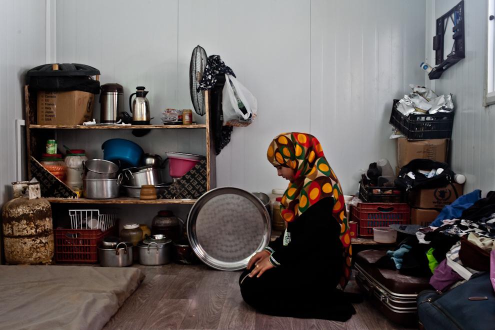 Fată siriancă se roagă printre lucrurile pe care ea şi familia sa au reuşit să le aducă cu ei din Siria în tabăra de refugiaţi Za'atari, Iordania.