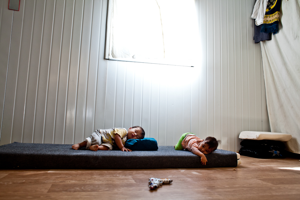 Copii sirieni dorm pe o saltea din containerul primit ca adăpost în tabăra de refugiaţi Za'atari, Iordania.