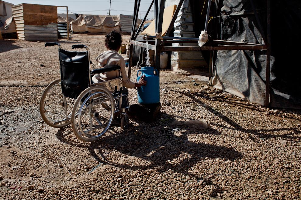 Fată aflată în scaunul cu rotile ia apă pentru familia sa de la una din sursele amplasate în tabăra de refugiaţi sirieni Za'atari, Iordania.