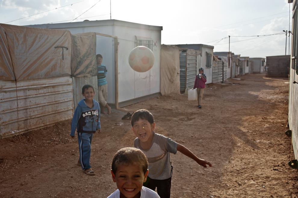 Copii sirieni joacă fotbal pe străzile prăfuite ale taberei de refugiaţi Za'atari, Iordania.