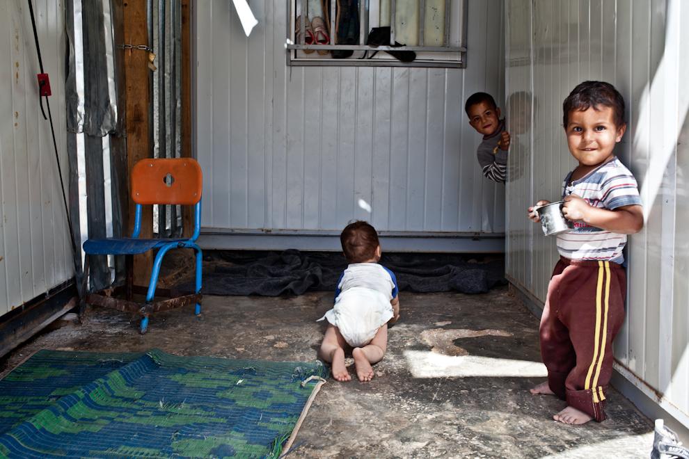 Copii refugiaţi sirieni se joacă în faţa containerelor în care locuiesc, în tabăra de refugiaţi Za'atari, Iordania.