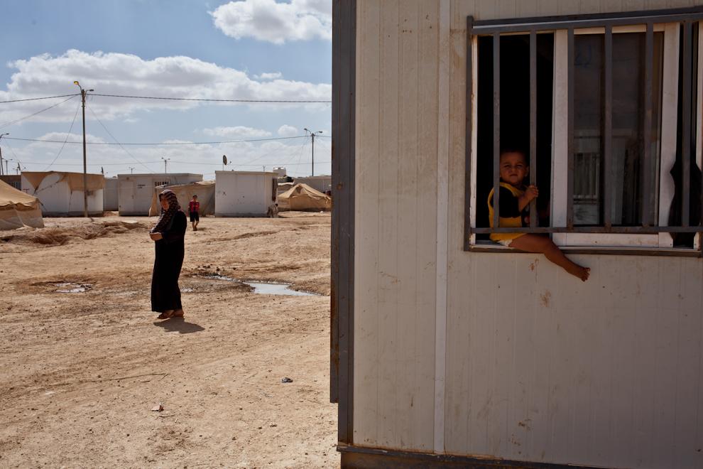 Bebeluş sirian stă pe marginea ferestrei cu gratii a containerului în care familia sa locuieşte, în tabăra de refugiaţi Za'atari, Iordania.