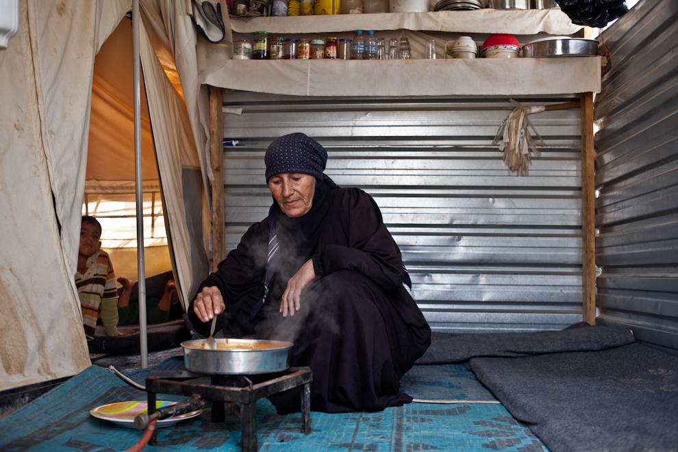 Bătrână din Siria găteşte la un aragaz improvizat prânzul pentru familia sa, în cortul din tabara de refugiaţi sirieni Za'atari, Iordania.