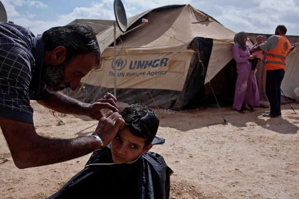 Bărbat sirian îşi tunde fiul, în spatele cortului în care aceştia trăiesc în tabăra de refugiaţi sirieni Za'atari, Iordania.