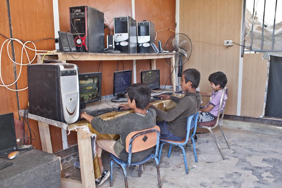 Copii sirieni se joacă pe calculator în una din salile de jocuri improvizate pe strada principală a taberei Za'atari, stradă cunoscută printre refugiaţi sub numele de Champs-Élysées.