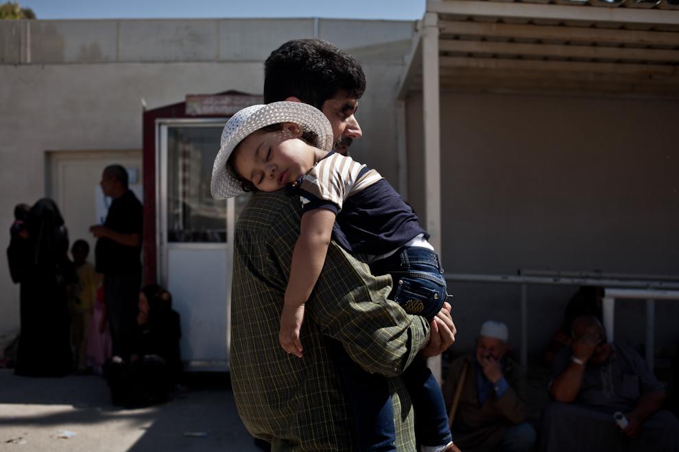 Refugiat sirian ţinându-şi copilul adormit în braţe aşteaptă în faţa Centrului pentru refugiaţi urbani al Înaltului Comisariat pentru Refugiaţi al Naţiunilor Unite (UNHCR) din Amman, Iordania.