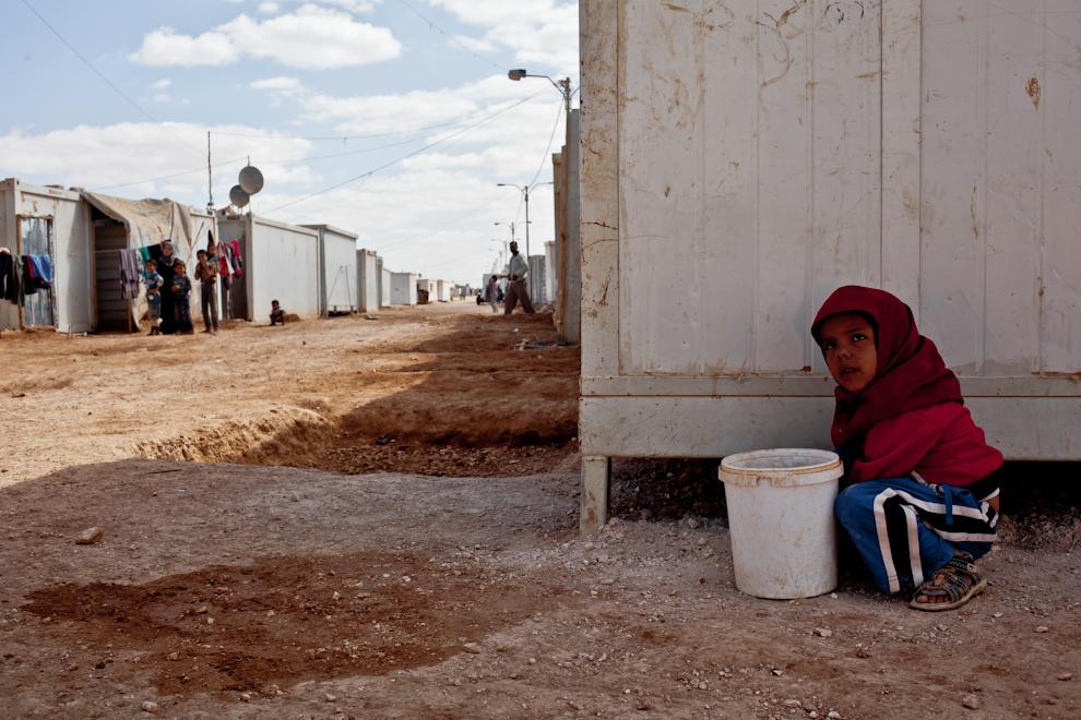 O fetiţă siriancă strânge pietriş într-o găleată, pe una din străduţele din Za'atari. Gropile săpate pe străzi servesc la evaporarea apei folosite în gospodării.