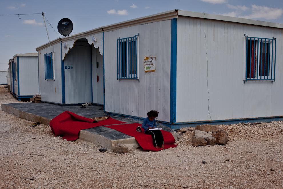 O fetiţă din Za'atari îşi face temele în faţa casei. Unii refugiaţi sirieni îşi construiesc din prefabricatele UNHCR locuinţe mai spaţioase, care îi fac să se simtă cât de cât acasă, fie şi într-o tabără de refugiaţi.
