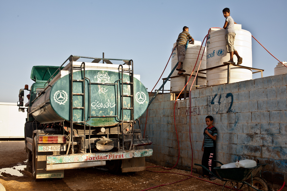 Copii sirieni ajută la încărcarea unei cisterne cu apă. Patru milioane de litri de apă sunt consumaţi zilnic în tabăra de refugiaţi Za'atari, Iordania.