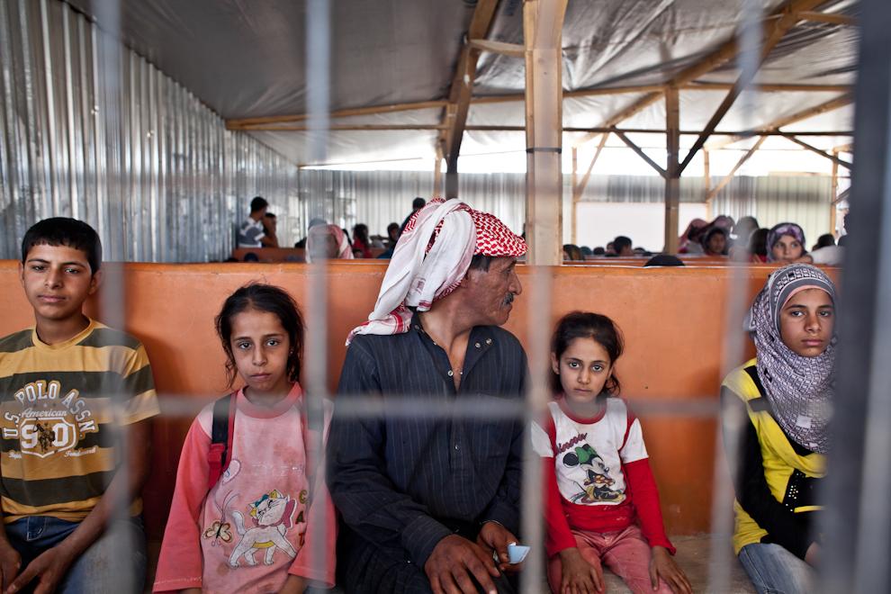 Refugiaţi sirieni aşteaptă în spaţiul de procesare a noilor refugiaţi ajunşi în tabăra Za'atari din Iordania. În unele zile, numărul sirienilor înregistraţi în Za'atari ajungea la 2500.