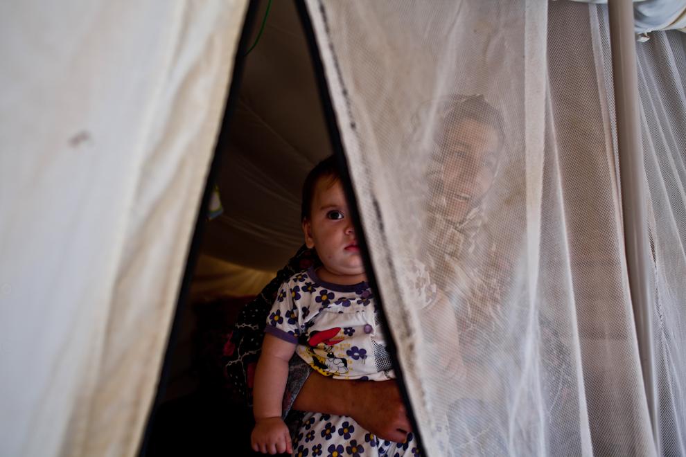 Femeie sirianca îşi ţine copilul în braţe în cortul familiei din tabara Za'atari din Iordania. Peste 50% din refugiaţii sirieni înregistraţi în Iordania sunt copii.
