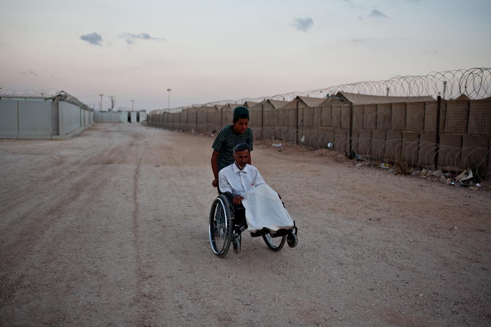 Adolescent sirian împinge scaunul cu rotile al unui bărbat vârstnic pe una din străzile taberei de refugiaţi sirieni Za'atari, Iordania.