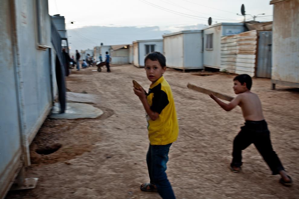 Copii sirieni refugiaţi din calea războiului civil se joacă cu puşti improvizate printre containerele ce le servesc drept adăpost în tabara Za'atari, Iordania.