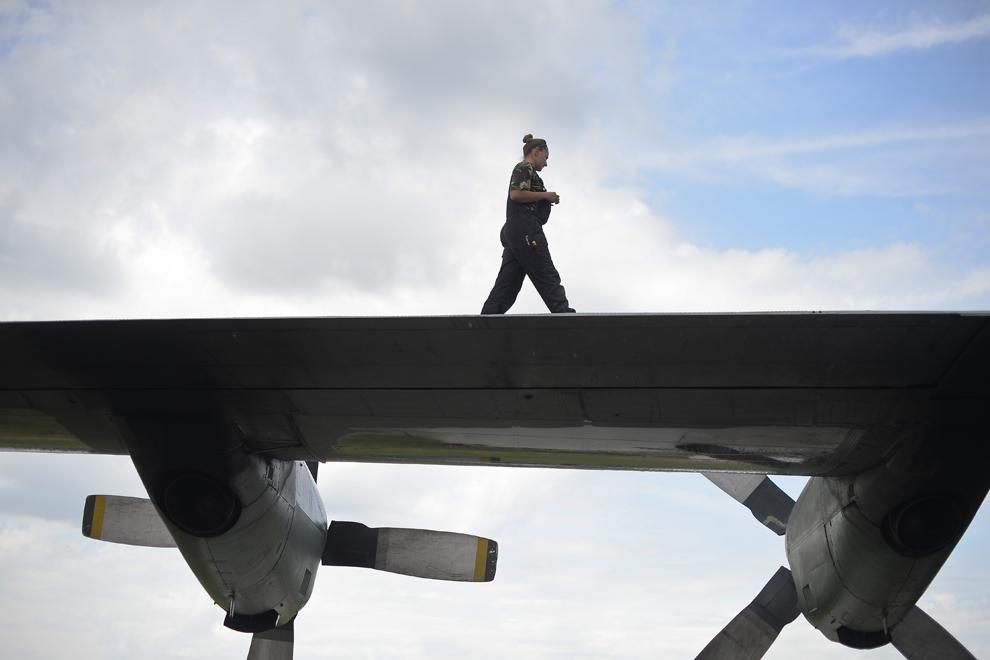 Mecanici fac verificări unei aeronave C-130 Hercules, după ce a fost folosită la transportarea unei părţi a grupului de 84 de cetăţeni români repatriaţi din Fâşia Gaza, luni, 14 iulie, 2014.