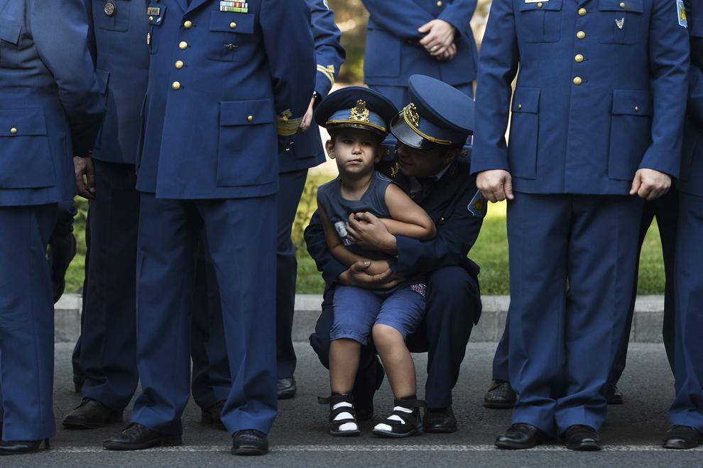 Un copil participă, alături de militari şi personal auxiliar din cadrul aviaţiei române, la o ceremonie militara şi religioasă, cu ocazia Zilei Aviaţiei Române şi a Forţelor Aeriene, la Monumentul Eroilor Aerului din Piaţa Aviatorilor din Bucureşti, duminică, 20 iulie 2014.