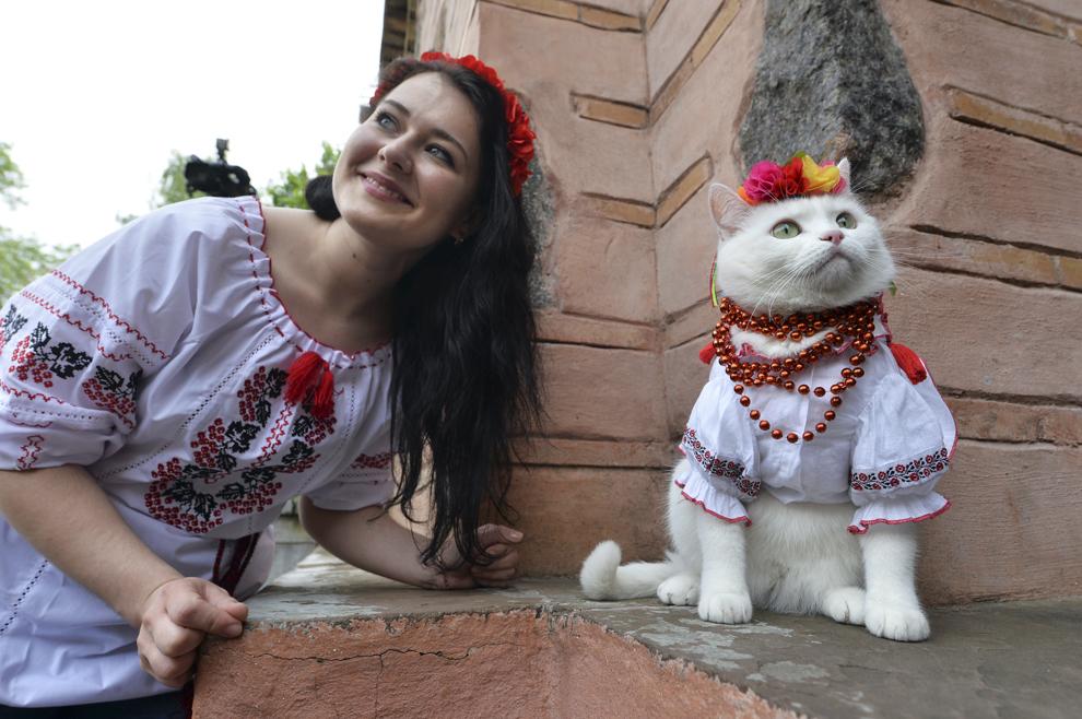 O fată pozează cu o pisică ce poartă o cămaşă tradiţională ucraineană brodată, în timpul unui festival tradiţional, în Kiev, sâmbătă, 17 mai 2014.
