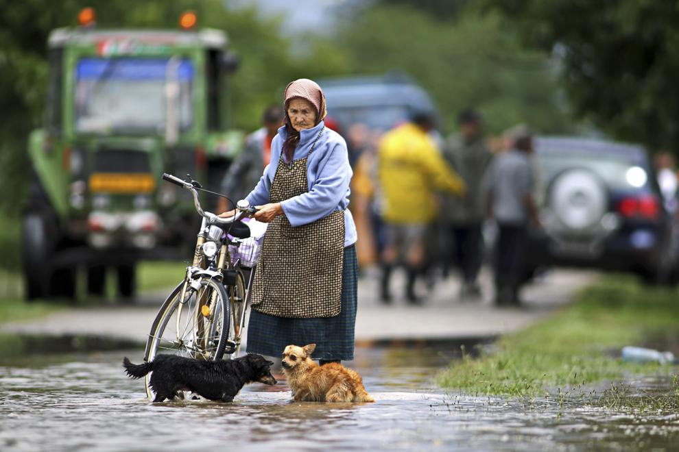 O femeie merge cu o bicicletă prin apă, ca urmare a revărsării râului Bârzava, în oraşul Gătaia din judeţul Timiş, joi, 31 iulie 2014.