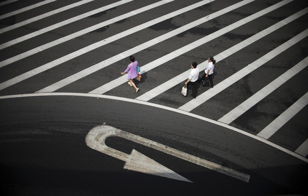 Persoane traversează strada în districtul financiar Lujiazui din Pudong, Shanghai, China luni, 1 septembrie 2014.