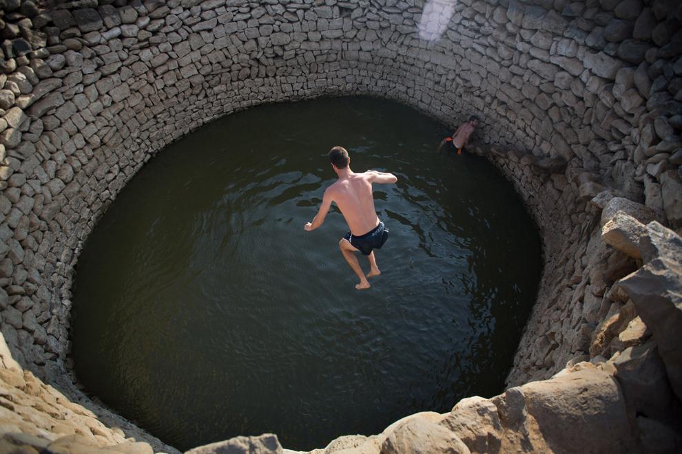 Localnici din Israel fac baie într-o piscină antică în apropierea aşezării Ein Zivan ce face parte din teritoriul anexat de Israel la graniţa cu Siria, luni, 1 septembrie 2014.