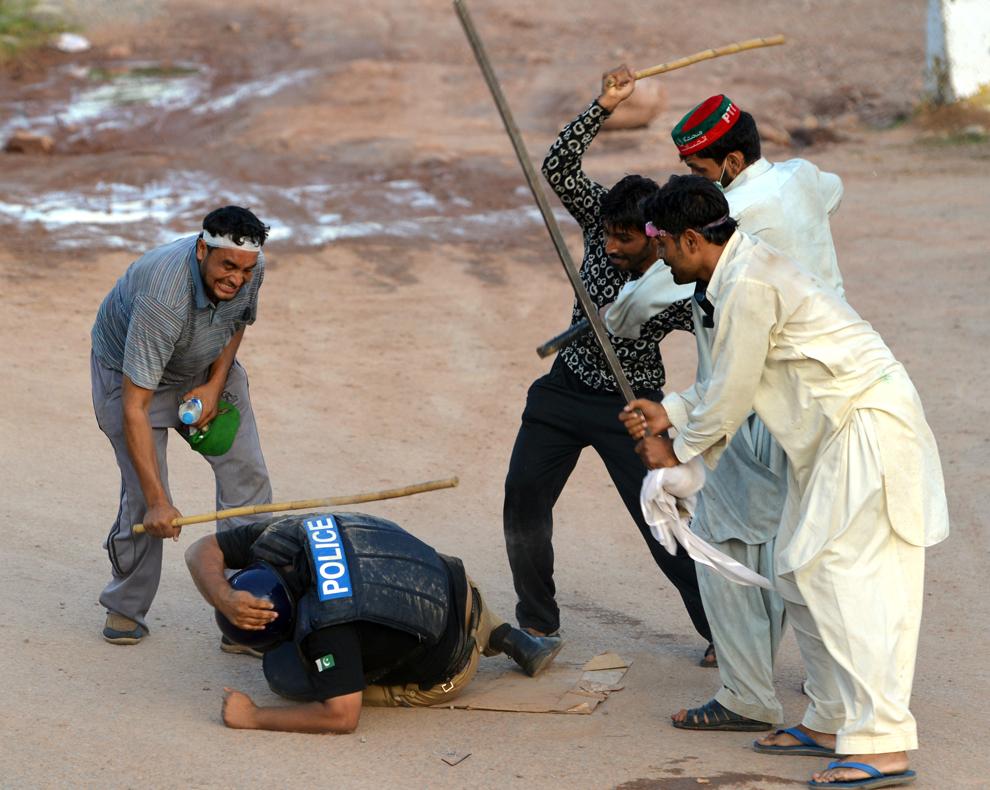 Suporteri pakistanezi ai jucătorului de crichet devenit politician, Imran Khan şi ai clericului canadian Tahir ul Qadri agresează un poliţist, în timpul unui protest anti-guvernamental, în Islamabad, Pakistan, luni, 1 septembrie 2014.