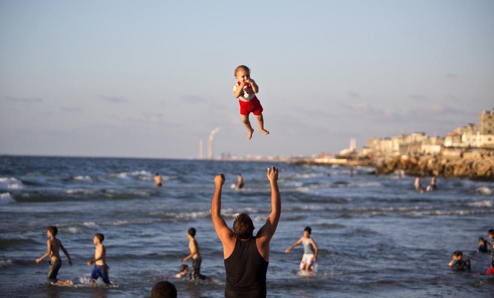 Un bărbat palestinian se joacă cu un copil pe plajă, în oraşul Gaza, duminică, 7 septembrie 2014.