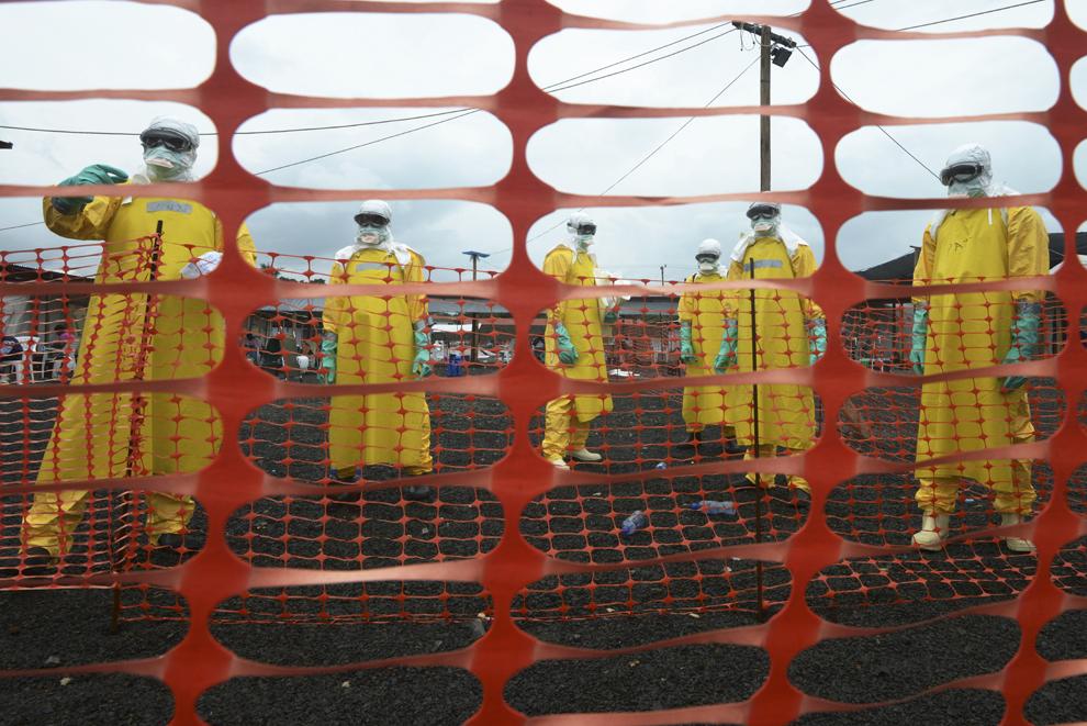 Muncitori purtând costume de protecţie personală stau în interiorul zonei contaminate la spitalul Elwa condus de organizaţia Medici Fără Frontiere, în Monrovia, Liberia, duminică, 7 septembrie 2014.