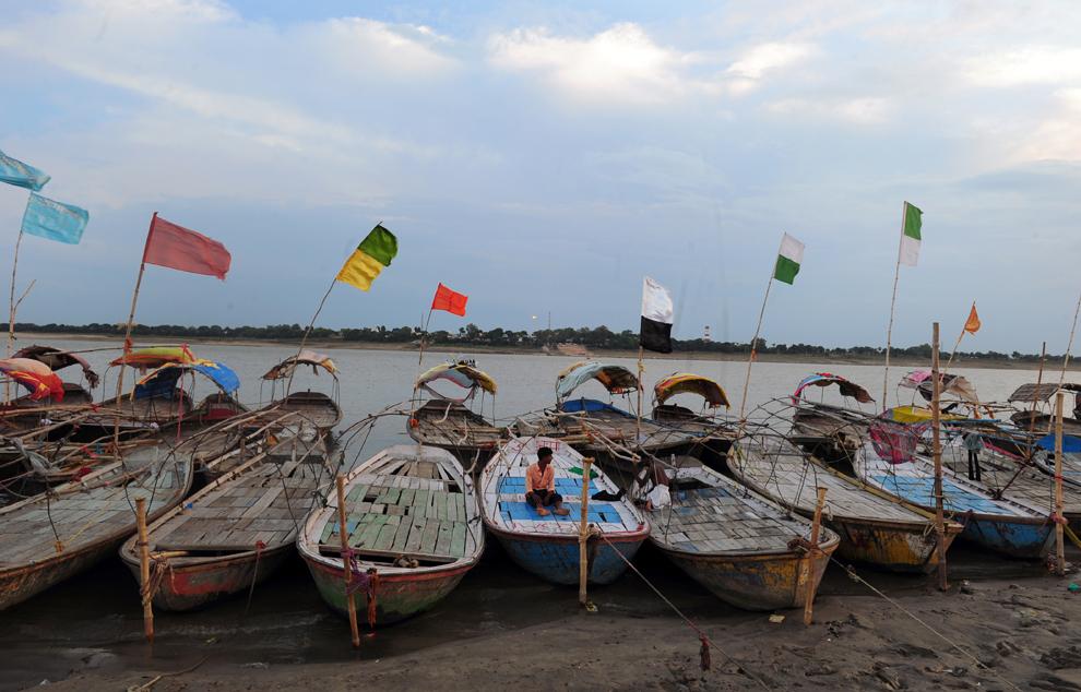 Un pescar indian stă pe barca sa în timp ce aşteaptă pelerini la Sangram, confluenţa râurilor Gange, Yamuna şi Saraswati, în Allahabad, India, marţi, 2 septembrie 2014.