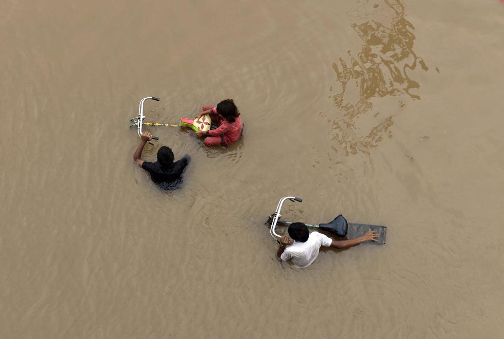 Localnici pakistanezi înfruntă apele revărsate ale unui râu, în urma unor inundaţii în Lahore, Pakistan, joi, 4 septembrie 2014.