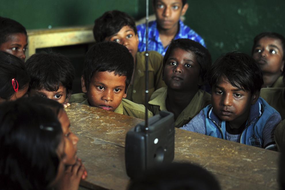 Elevi indieni stau adunaţi în jurul unui aparat de radio pentru a asculta o transmisiune în care premierul indian, Narendra Modi, ţine un discurs cu ocazia zilei profesorului, într-o şcoala din Bakshi Kala, Allahabad, India, vineri, 5 septembrie 2014.
