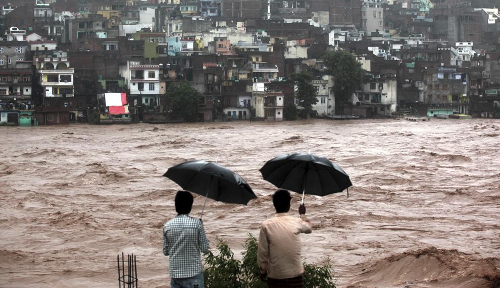 Persoane privesc spre case ameninţate de apele revărsate ale râului Tawi, în Jammu, India, sâmbătă, 6 septembrie 2014.