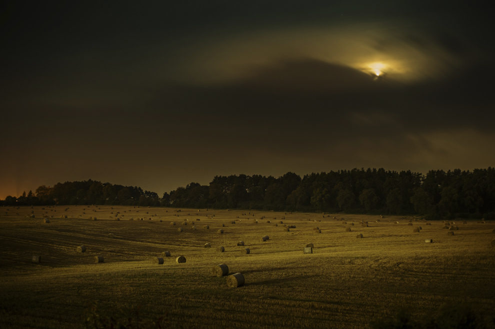 Fotografie cu expunere lungă : Un câmp acoperit cu baloţi de fân poate fi văzut în apropierea ruinelor castelului Spis, în satul Zehra, Slovacia, marţi, 2 septembrie 2014.