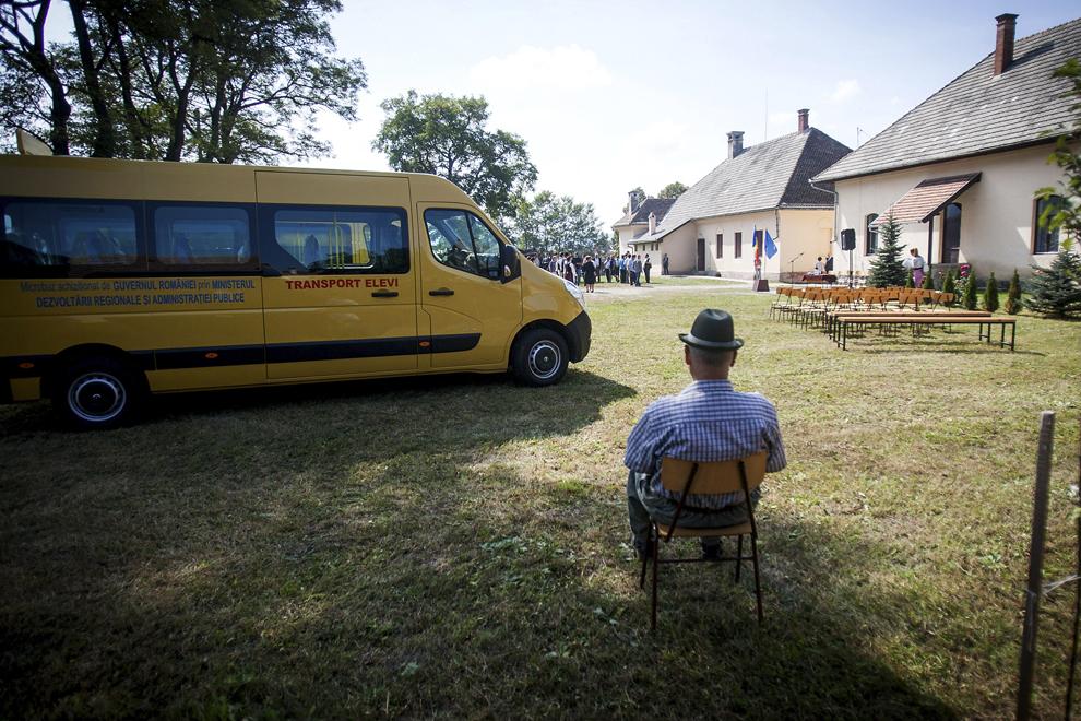 Un bărbat stă la umbră, înaintea ceremoniei de înmânare a cheilor microbuzelor primite de şcoli din partea Guvernului României, în comuna Cozmeni din judeţul Harghita, joi, 11 septembrie 2014.