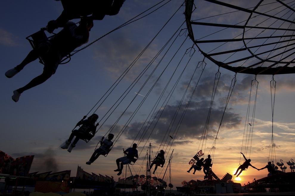 Tineri se dau într-un carusel, în timpul Târgului de Toamnă de la Titu, sâmbătă, 13 septembrie 2014.