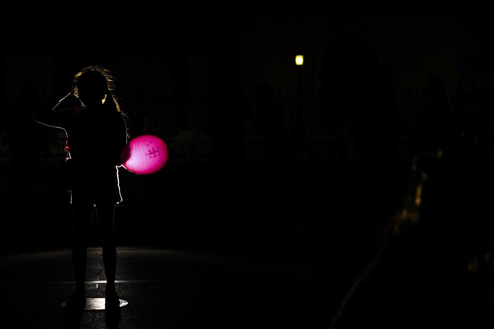"""O fetiţă, luminată din spate de un reflector, ţine în mână un balon, în timpul spectacolului """"Aprinde Magenta"""", în cadrul căruia Romtelecom şi Cosmote România au lansat noul brand """"Telekom România"""", în Bucureşti, sâmbătă, 13 septembrie 2014."""