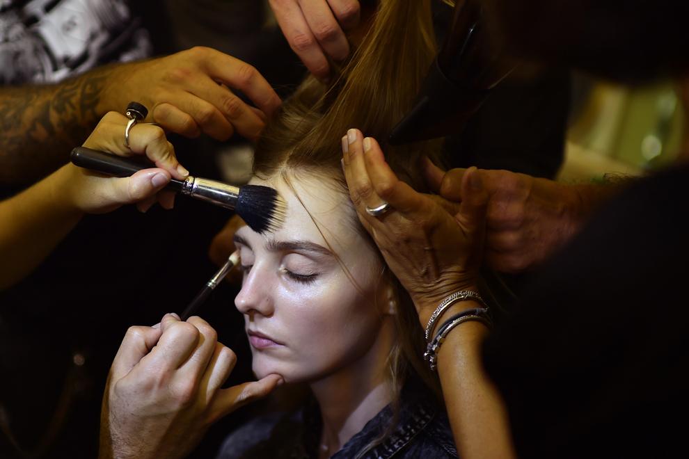 Un model este machiat în culisele show-ului Fay, parte din Săptămâna Modei primăvară/vară din Milano, în Milano, Italia, miercuri, 17 septembrie 2014.