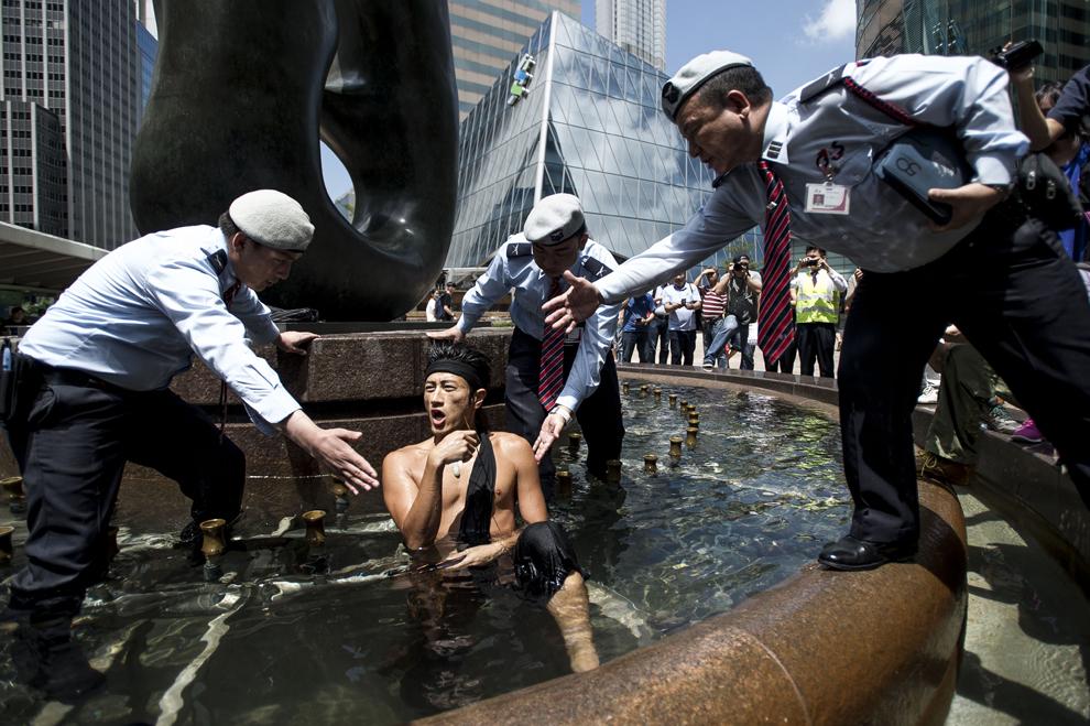 Ofiţeri de securitate roagă un protestatar să iasă dintr-o fântână înaintea unei conferinţe, în apropiere de cladirea Bursei de Valori din Hong Kong, joi, 18 septembrie 2014.