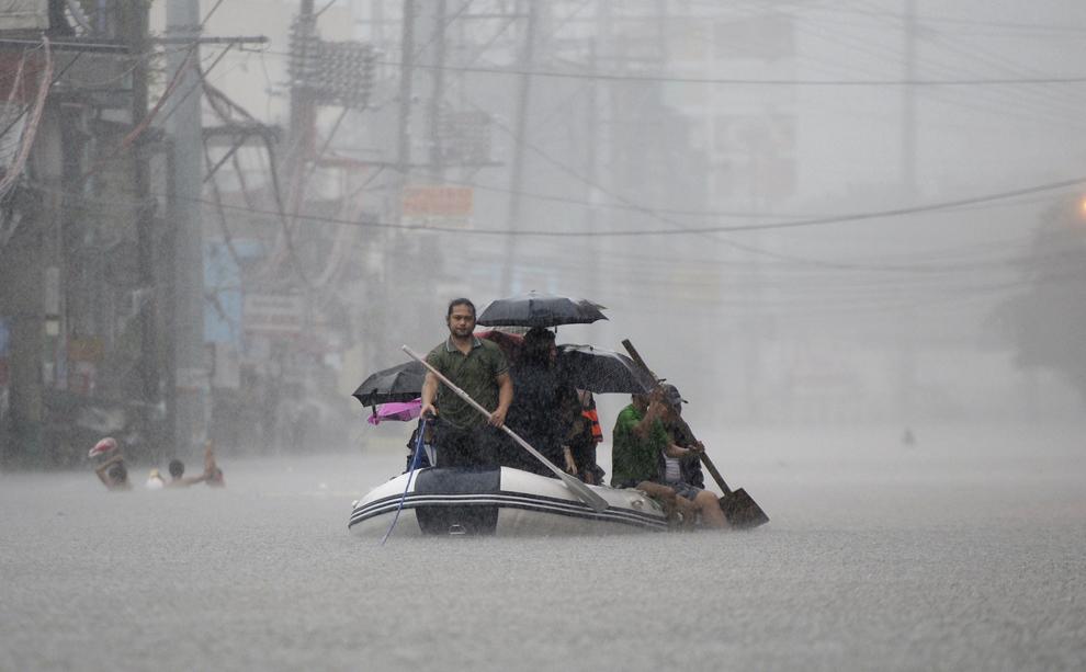 Sinistraţi sunt transportaţi cu o barcă prin apele ce au inundat Manila în urma furtunii tropicale Fung-Wong, în Manila, Filipine, vineri, 19 septembrie 2014.