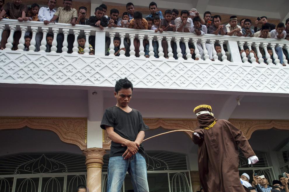 Un ofiţer mascat loveşte cu o nuia un locuitor din Banda Aceh care a jucat la pariuri, în Banda Aceh, Indonezia, vineri, 19 septembrie 2014.