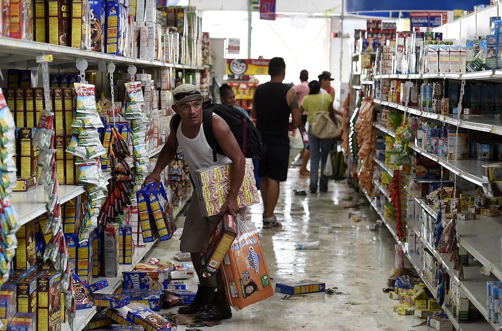Oameni fură dintr-un supermarket după ce uraganul Odile a dărâmat mai mulţi copaci şi linii de înaltă tensiune, în San Jose del Cabo, Mexic, luni, 15 septembrie 2014.