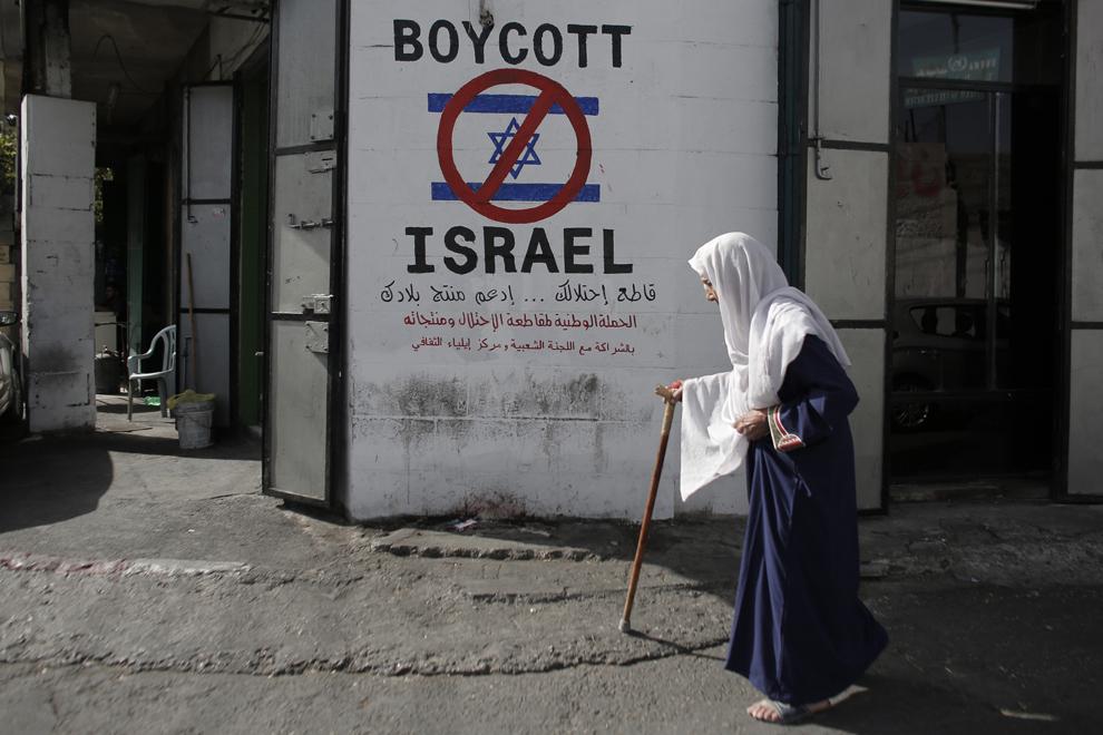 O femeie de origine palestiniană, trece pe lângă un zid pe care este inscripţionat îndemnul de a boicota produsele israeline, în tabăra de refugiaţi al-Azzeh de lângă Bethlehem,  miercuri, 17 septembrie 2014.