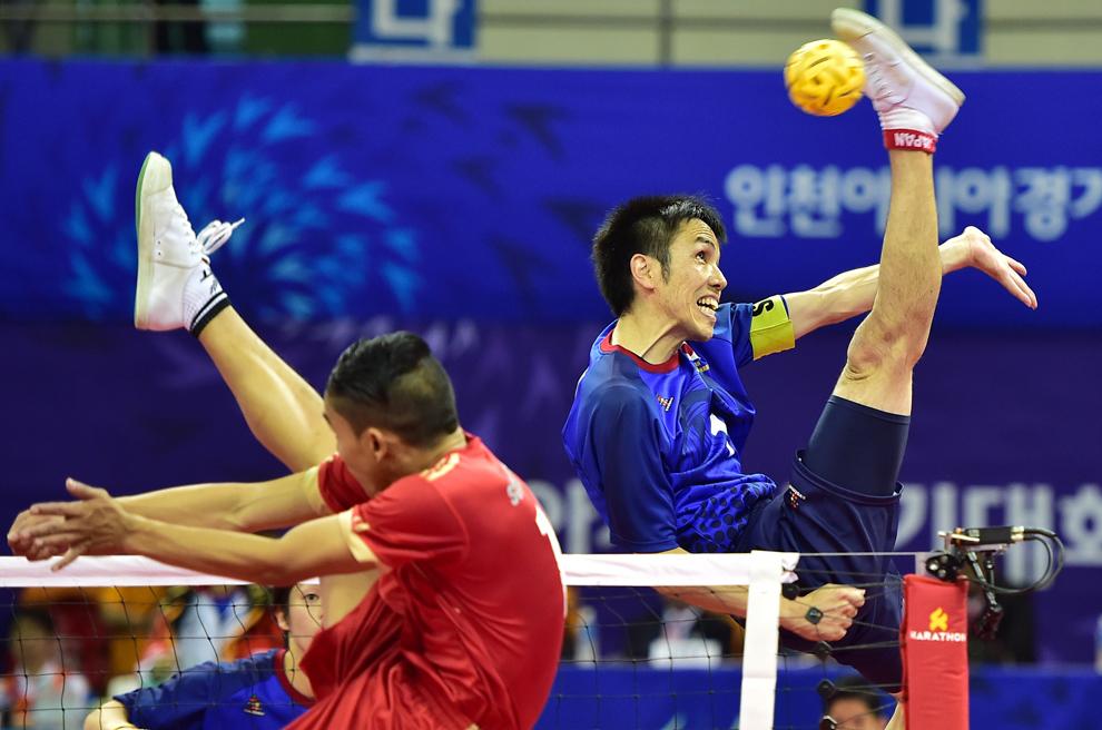 Japonezul Seiya Takano (D) returnează mingea jucatorului Mohamad Farhan Amran (S) din Singapore, în timpul meciului dublu de sepaktakraw (volei cu piciorul), din cadrul Jocurilor Asiatice 2014 în Bucheon, Republica Coreea, duminică, 21 septembrie 2014.