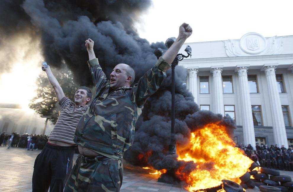 Un grup de protestatari reacţionează în timp ce cauciucuri ard în apropiere de parlamentul Ucrainean, în Kiev, Ucraina, marţi, 16 septembrie 2014.
