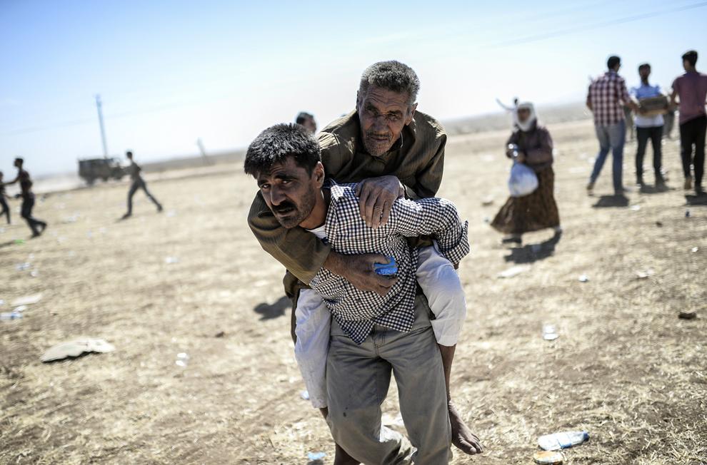 Un bărbat ţine pe umeri un bărbat sirian/kurd, după ce au traversat graniţa dintre Siria şi Turcia, în apropiere de orasul Suruc, provincia Sanliurfa, Turcia, vineri, 20 septembrie 2014.