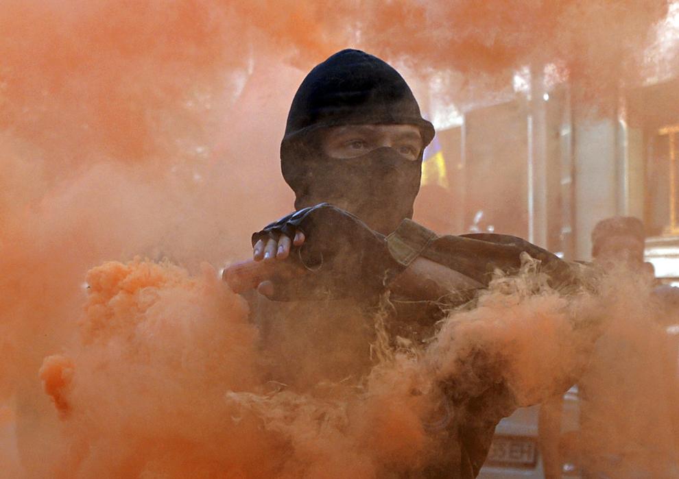 Un protestatar aruncă o fumigenă în timpul unei demonstraţii în apropierea palatului prezidenţial din Kiev, miercuri, 17 septembrie 2014.
