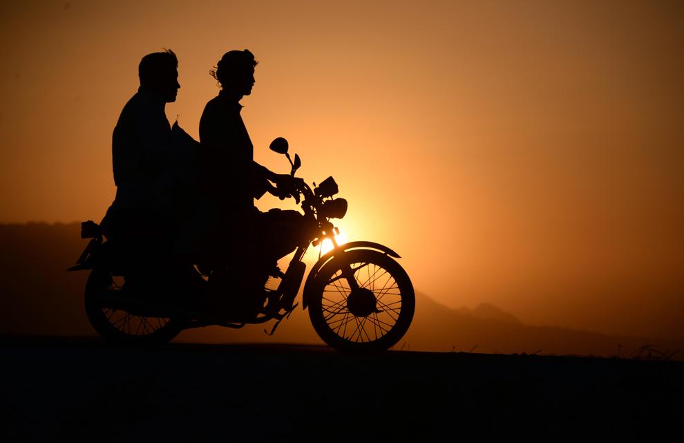 Bărbaţi afgani se plimbă cu motocicleta la apusul soarelui, la periferia oraşului Mazar-i-sharif, Afganistan, vineri, 19 septembrie 2014.