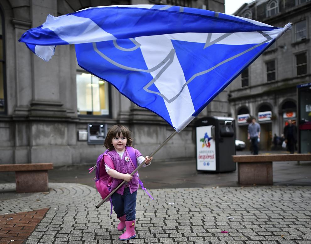 """Un copil se joacă cu steagul pro-independenţă """"Yes"""" înaintea referendumului pentru independenţa Scoţiei, în Aberdeen, Scoţia, luni, 15 septembrie 2014."""