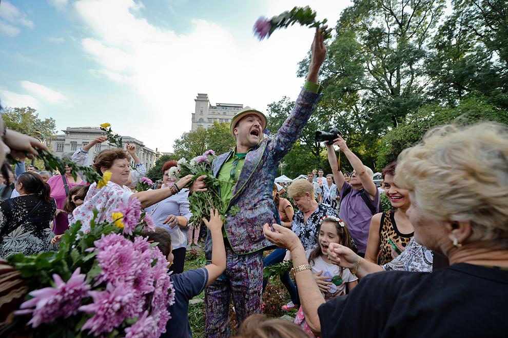 Persoane aruncă flori în mulţime, în timpul unei bătăi cu flori, organizate cu ocazia aniversării a 555 de ani de atestare documentară a Bucureştiului, în parcul Cişmigiu din Bucureşti, duminică, 21 septembrie 2014.
