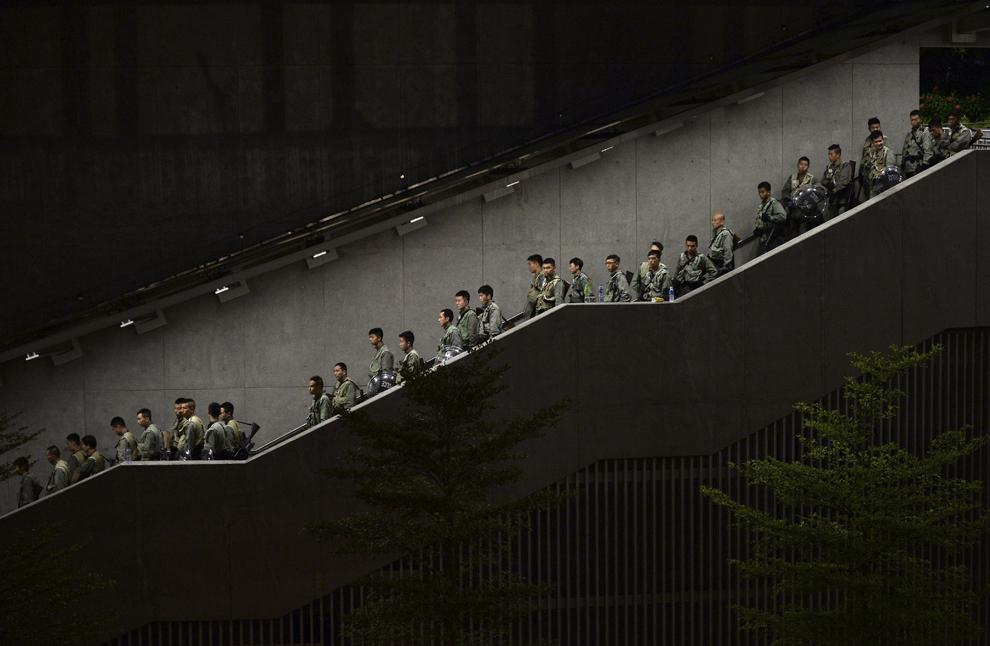 Poliţişti coboară scări în timp ce protestatari pro-democraţie se strâng pentru un miting desfăşurat în apropiere de sediul guvernului din Hong Kong, China, luni, 29 septembrie 2014.
